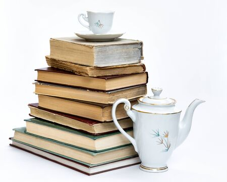 a stack of old books and an elegant coffee set. On white background