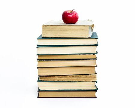 a stack of old books. A red apple lies on top. The concept of an idea came like a Newtons apple. On white background