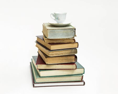 a stack of old books. Upstairs is an elegant coffee cup and saucer. On white background. 版權商用圖片