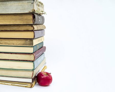 a stack of old books. Nearby lies a red apple. The concept of an idea came like a Newtons apple. On white background.