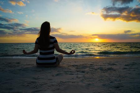 mujer mirando el horizonte: Niña sentada en la playa contra el cielo y el océano. Una puesta de sol en el mar en el horizonte. Sensación de libertad y felicidad. Estilo de vida, la recreación, la soledad, la meditación. Hermosa puesta de sol en la playa del océano.
