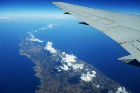 The plane is flying over the island of Cyprus. Airplane wing in flight from window.