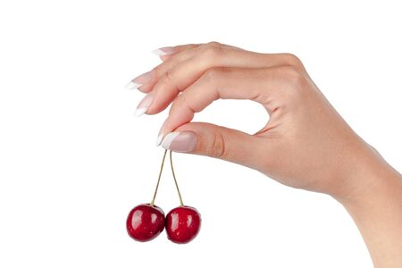 Closeup of juicy cherry in the beautiful female hand isolated on white background, with clipping path