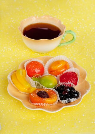 Cup of tea and fruit candy - strawberry, apricot, peach, currants, banana, pear, apple on the plate on yellow background. Time to drink tea concept.