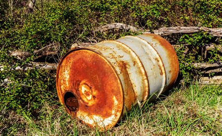 Closeup of old rusty barrel of fuel on a sunny day in the forest. Environmental pollution concept. Stock Photo