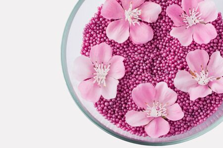 Closeup of aromatic pink pearl bath beads and flowers in glass bowl, isolated on white, with clipping path. Healthcare and SPA, care for skin concept.