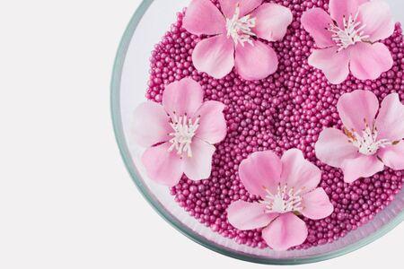 elasticidad: Primer de las gotas y de las flores rosadas aromáticas del baño de la perla en el bol de vidrio, aislado en blanco, con el camino de recortes. Cuidado de la salud y SPA, cuidado del concepto de la piel.
