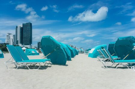 Cityscape of South Miami Beach, Florida. Beach near ocean with turquoise ?haise lounges and sun umbrellas. Summer vacation concept.