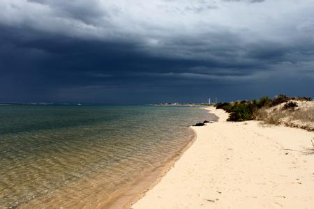 Portugal. Algarve. Ilha deserta. Sand and ocean before storm on dark blue sky background, horizontal view.