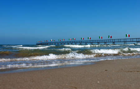 Italy. Emilia-Romagna. Rimini. Group of flags of italy and sea on blue sky background. Horizontal view