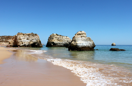 soggy: Portugal, Algarve, Portimao. Rocks in the atlantic ocean and wave on blue sky background, horizontal view