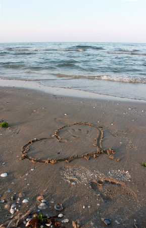 valentine s day beach: Heart drawn on the sand near sea, vertical view Stock Photo