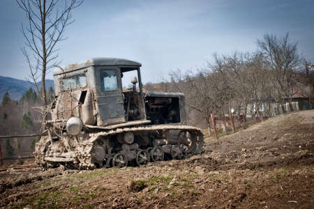 an old tractor is abandoned in dirt
