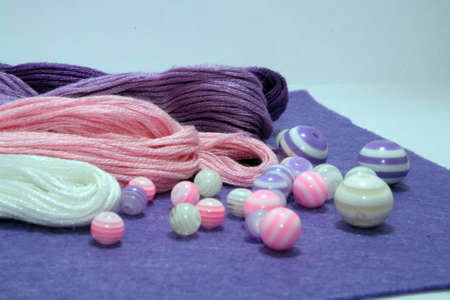 Beads and sewing threads for embroidery on a felt background. Space for text.