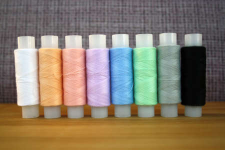 Colorful yarn on spool, cotton. Colorful sewing threads on white background. Space for text.
