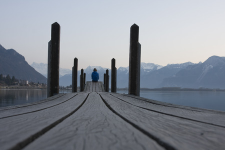 A man sitting footbridge over the water. photo