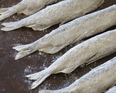 tatty: Small fish (capelin) sprinkled with flour before baking Stock Photo