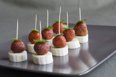 Fruit canape - banana and strawberry with mint leaf photo