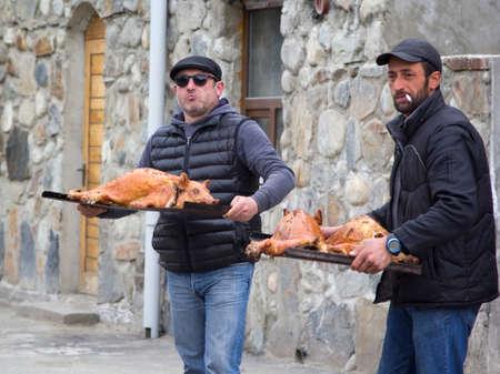 mestia: MESTIA, GEORGIA  - APRIL 18 : Two Georgian men holding trays of roasted pigs. April 18, 2015, in Mestia, Georgia. Editorial