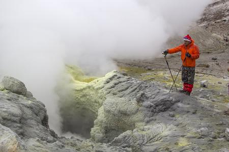 fumarole: A tourist observes an active fumarole, producing volcanic gas. Kamchatka, Russia