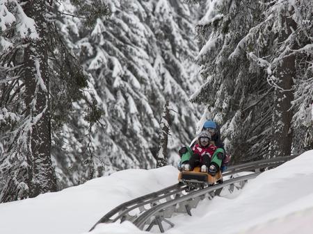 toboggan: KOPAONIK, SERBIA - February, 05. Boy and girl sledding on the toboggan. February 05, 2015 in Kopaonik, Serbia Editorial