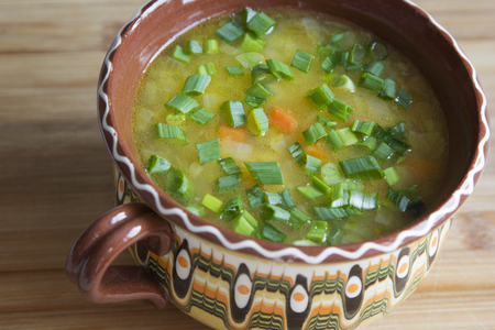 Vegetable soup with green onion in a clay bowl.