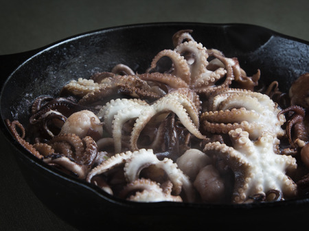 Mini octopus in the process of roasting on a cast iron pan.