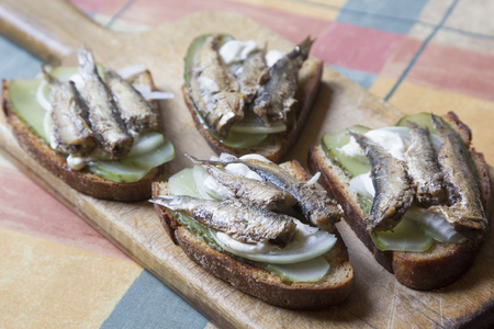 Snack sandwiches with sprats and pickles.