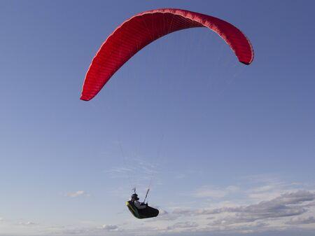 A paraglider athlete flies a red paraglider.