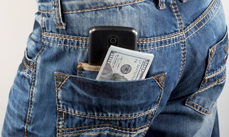 advances: Money and mobile phone in a hip-pocket of trousers Stock Photo