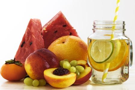 Frische Fruchtscheiben. Fruchtwasser. Wassermelone, Pfirsich, Orange, Persimmon Früchte.