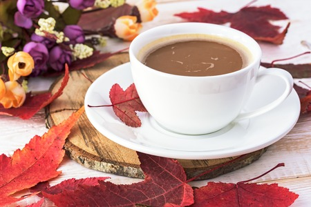 macchiato: Cup of coffee on table. Coffee with milk. Red autumn leaves