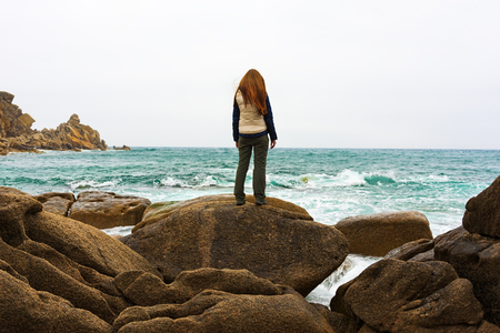 mujer golpeada: Depressed woman staring into the distance. Girl standing on rock