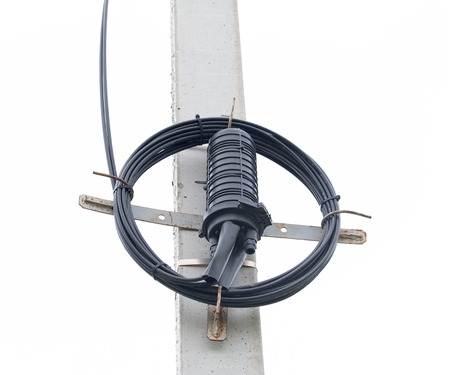 Optical cable on the pole. Closure Optical Fiber on white background 스톡 콘텐츠