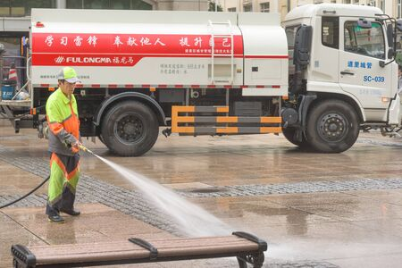 Harbin, Heilongjiang, China - September 2018: Man washes the pavement. Worker cleaning the street Editöryel
