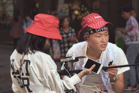 Harbin, Heilongjiang, China - September 2018: Young man and woman working as blogger. Blogger writes video report Editöryel