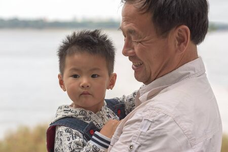 Harbin, Heilongjiang, China - September 2018: Portrait of Asian boy and grandfather. Grandfather with grandson Editöryel