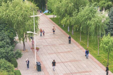 Harbin, Heilongjiang, China - September 2018: Street with green trees. View of a pedestrian street.