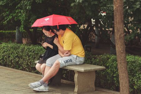 Harbin, Heilongjiang, China - September 2018: Couple sitting on bench. Man and woman under umbrella Editöryel