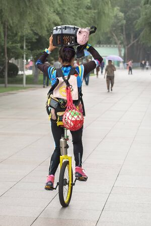 Harbin, Heilongjiang, China - September 2018: Girl driving unicycle outdoors. Girl on the unicycle Editöryel