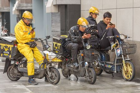 Harbin, Heilongjiang, China - September 2018: Delivery man on motor scooter. Guys look at smartphones Editöryel