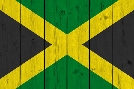 Jamaica flag painted on old wood plank. Patriotic background. National flag of Jamaica