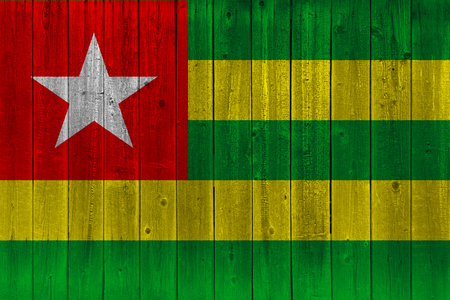 Togo flag painted on old wood plank. Patriotic background. National flag of Togo