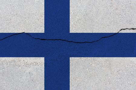 Finland flag on concrete wall with crack. Patriotic grunge background. National flag of Finland