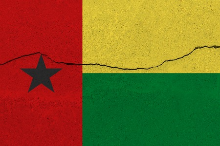 Guinea-Bissau flag on concrete wall with crack. Patriotic grunge background. National flag of Guinea-Bissau Stock Photo