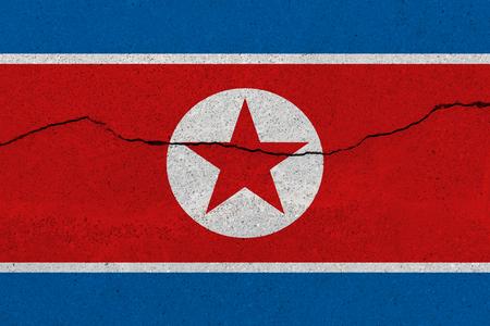 North Korea flag on concrete wall with crack. Patriotic grunge background. National flag of North Korea Imagens