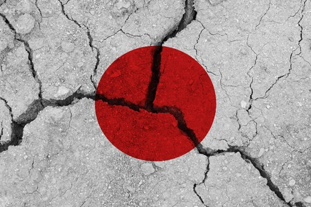 Japan flag on the cracked earth. National flag of Japan. Earthquake or drought concept Stock Photo