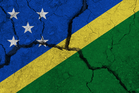 Solomon Islands flag on the cracked earth. National flag of Solomon Islands. Earthquake or drought concept Stock Photo