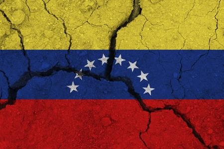 Drapeau du Venezuela sur la terre craquelée. Drapeau national du Venezuela. Concept de tremblement de terre ou de sécheresse Banque d'images
