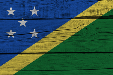 Solomon Islands flag painted on old wood plank. Patriotic background. National flag of Solomon Islands